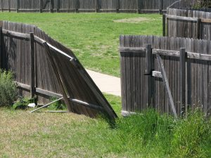 Storm damaged privacy fence with broken wooden post