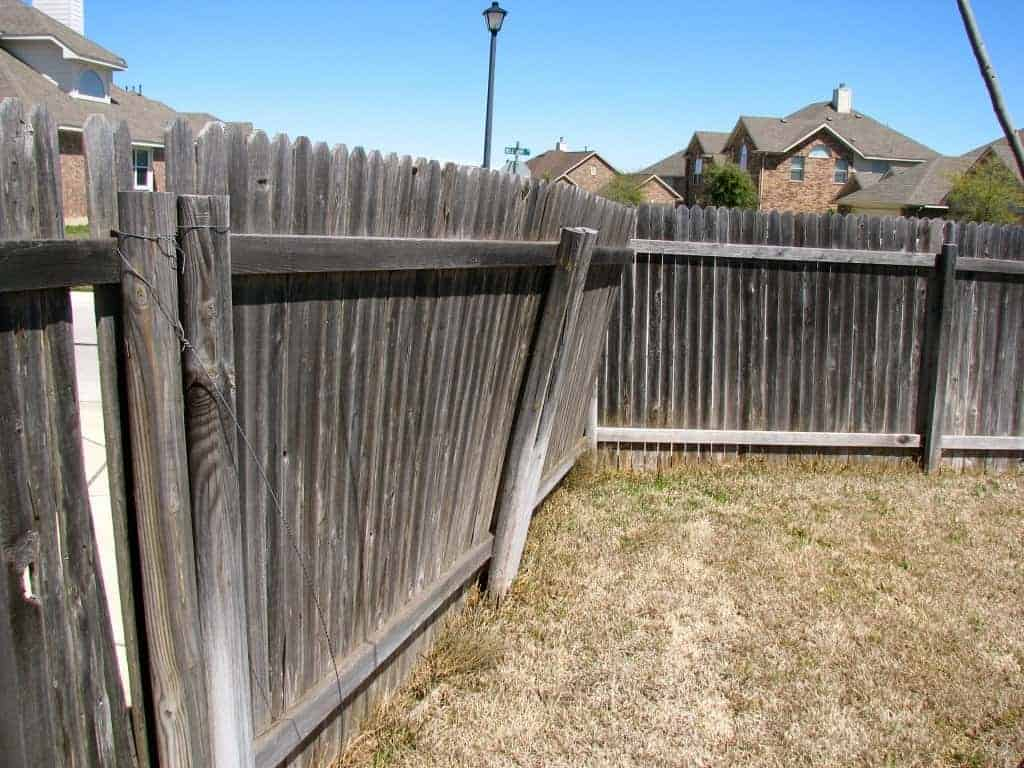 Leaning privacy fence panel from storm damage